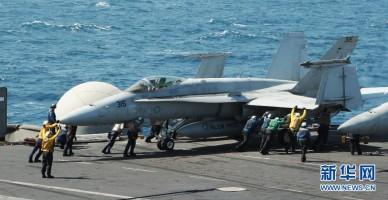"""这张美国海军8月8日提供的照片显示,在海湾地区执行任务的""""乔治·H·W·布什""""号航空母舰上,地勤人员指挥一架F/A-18C大黄蜂战斗机。美国五角大楼8日说,美军当天已向""""伊拉克和黎凡特伊斯兰国""""极端组织在伊拉克北部的目标发动空袭。两架F/A-18型战斗机参与了空袭。"""