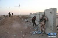 """8月8日,在伊拉克北部城市埃尔比勒郊外的一个检查站附近,库尔德武装组织成员躲避在掩体后。美国五角大楼8日说,美军当天已向""""伊拉克和黎凡特伊斯兰国""""极端组织在伊拉克北部的目标发动空袭。美国有线电视新闻网报道说,空袭目标是该组织用于攻击伊北部城市埃尔比勒库尔德守军的火炮阵地。美军向火炮阵地投下两枚500磅的激光制导炸弹。"""